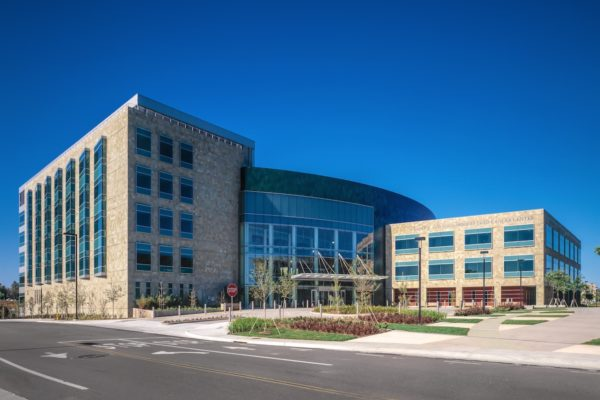 UCSD Cancer Center is a large building with a curved front that is made out of glass to reflect the blue sky