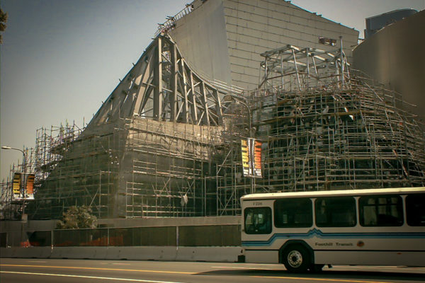 Disney Concert Hall under construction with a public bus in the bottom frame
