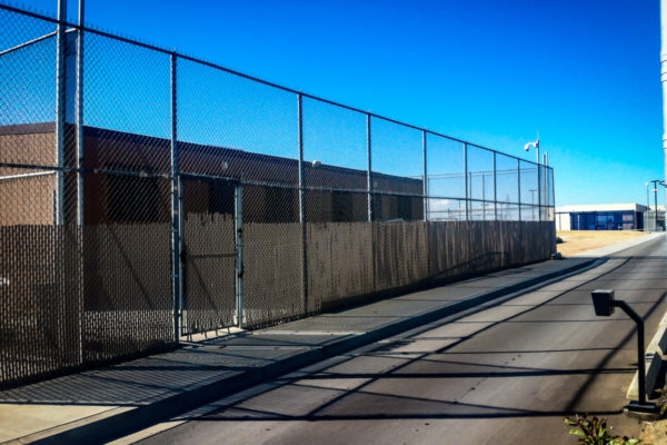 Adelanto ICE Processing Center chain link fence by street