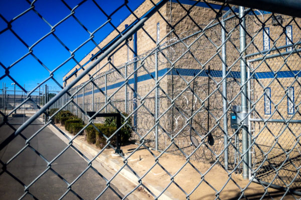 Adelanto ICE Processing Center view through chain fence