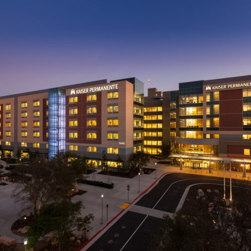 Kaiser Permanente illuminated at night with parking lot