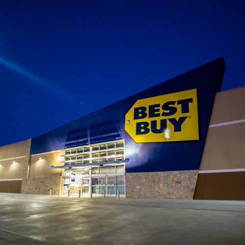 Best Buy illuminated at night with parking lot