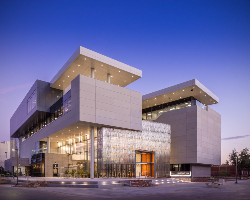 UNLV Hospitality Building front during a purple sunset that shows of amazing metal, glass, and use of light